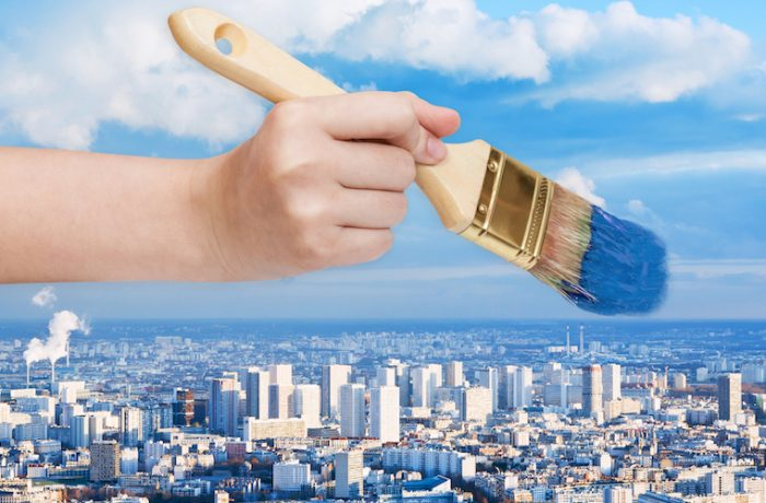 nature concept - hand with paintbrush paints blue sky over big city